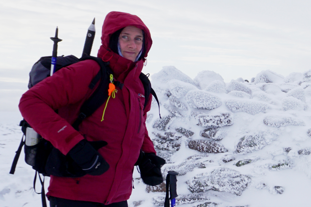Female winter mountaineer by cairn