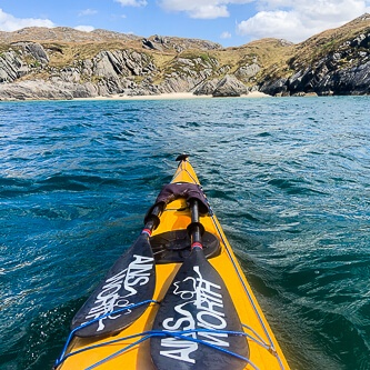Kayak approaching remote sandy beaches and rocky shorelines