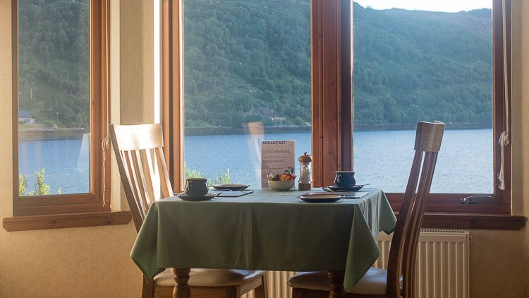 Dining table in bay window with views over Loch Sunart