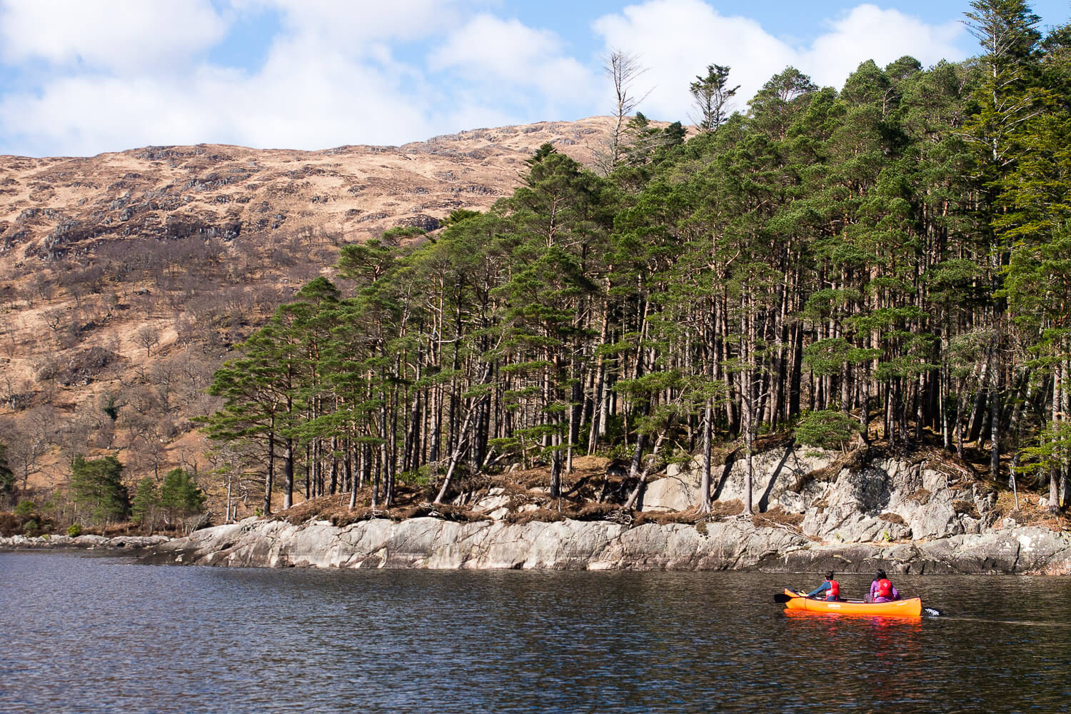 Canoe on Loch Shiel among rocky shoreline and ancient woodland